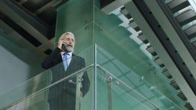 Dirigente aziendale senior che fa una chiamata facendo uso del cellulare nell'edificio per uffici moderno stock footage