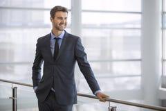 Dirigente bello sorridente dalla finestra dell'edificio per uffici moderno Fotografia Stock