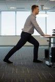 Dirigente che esegue allungando esercizio allo scrittorio Fotografia Stock