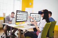 Dirigente che gode della cuffia avricolare aumentata di realtà con i colleghi all'ufficio creativo immagine stock