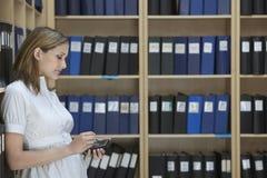 Dirigente che utilizza la cima della palma nel magazzino dell'archivio Immagini Stock Libere da Diritti