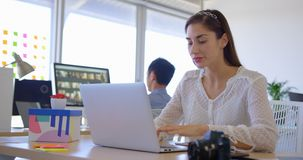 Dirigente femminile caucasico grazioso che lavora al computer portatile allo scrittorio 4k stock footage