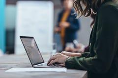 Dirigente femminile che per mezzo del computer portatile durante la presentazione immagine stock