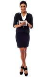 Dirigente femminile che per mezzo del cuscinetto di tocco, colpo integrale Fotografia Stock