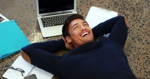 Dirigente maschio sorridente che si rilassa sul pavimento 4k archivi video