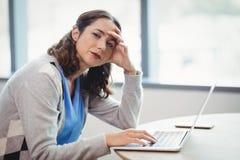 Dirigente stanco del ritratto che per mezzo del computer portatile allo scrittorio immagine stock libera da diritti