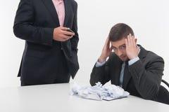 Dirigez fâché avec le jeune employé s'asseyant au bureau Photos libres de droits