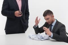 Dirigez fâché avec le jeune employé s'asseyant au bureau Photos stock