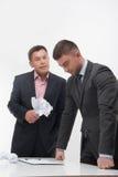 Dirigez fâché avec le jeune employé s'asseyant au bureau Photo libre de droits