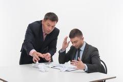 Dirigez fâché avec le jeune employé s'asseyant au bureau Photographie stock libre de droits