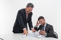 Dirigez fâché avec le jeune employé s'asseyant au bureau Image stock