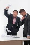Dirigez fâché avec le jeune employé s'asseyant au bureau Photographie stock