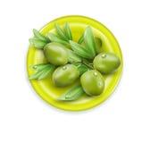 Dirigez la branche avec les olives vertes se trouvant d'un plat, sur le wh Photos libres de droits