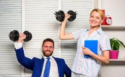 Dirigez la main d'augmenter de directeur d'homme d'affaires et de bureau avec des haltères Équipe intense d'affaires Habitudes sa image stock