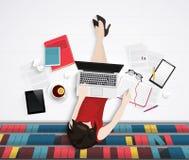 Dirigez la vue supérieure de la jeune femme se reposant sur le plancher avec le worlplace d'éléments Bureau de bibliothèque Image stock