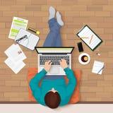 Dirigez la vue supérieure du jeune homme se reposant sur le plancher avec le lieu de travail d'ordinateur portable et d'éléments  Photos stock