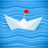 Dirigez le bateau de papier dans les ondes bleues de la mer Photo stock