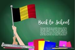 Dirigez le drapeau de la Belgique sur le fond noir de tableau Fond d'éducation avec le support de mains du drapeau de la Belgique illustration stock