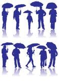 Dirigez les silhouettes homme, femmes et enfant avec le parapluie Photographie stock libre de droits