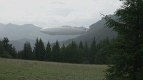 Dirigibile dello zeppelin nel paesaggio con le colline di legno video d archivio