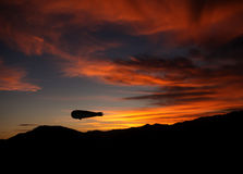 Dirigible aka airship aka blimp at dusk, sunset Stock Image