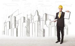 Dirija al hombre con el dibujo de la ciudad del edificio en fondo Foto de archivo