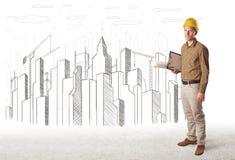 Dirija al hombre con el dibujo de la ciudad del edificio en fondo Fotografía de archivo libre de regalías