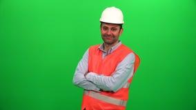 Dirija al trabajador que cruza sus brazos y que sonríe en la pantalla verde metrajes