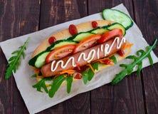 Dirija cachorros quentes feitos com vegetais, a salsicha suculenta e a rúcula Fotografia de Stock