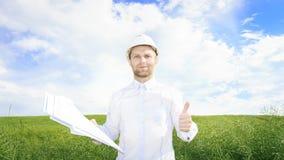 Dirija el constructor con los dibujos en manos en prado verde pedologist en el casco blanco en campo verde del verano en día sole imagen de archivo libre de regalías