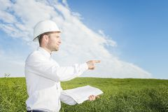 Dirija el constructor con los dibujos en sus puntos de las manos al emplazamiento de la obra del edificio geólogo en un prado ver foto de archivo
