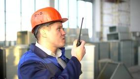 Dirija el constructor usando un Walkietalkie que da instrucciones en un emplazamiento de la obra dentro 4 K metrajes