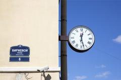 Dirija el reloj de la placa y de pared en la fachada del edificio Fotografía de archivo libre de regalías