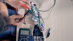 Dirija el trabajo con una mano biónica y un multímetro almacen de video