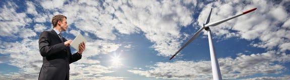 Dirija el uso la tableta, la turbina de viento del fondo y el cielo azul con el sol Foto de archivo libre de regalías
