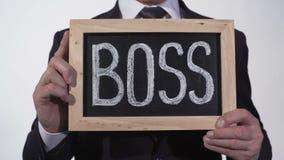 Dirija escrito no quadro-negro nas mãos do homem de negócios, gerente superior do corporaçõ, líder video estoque
