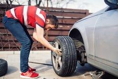 Dirija la instalación de los neumáticos del verano del funcionamiento en el coche gris foto de archivo libre de regalías