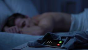 Dirija la llamada mientras que varón cansado que duerme profundamente en el fondo, negocio agotador metrajes