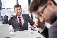 Dirija los papeles que lanzan en el colega del trastorno en la reunión de negocios foto de archivo