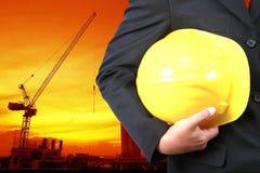 Dirija sostener el casco amarillo para la seguridad de los trabajadores en backgroun Fotografía de archivo libre de regalías