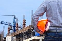 Dirija sostener el casco de seguridad amarillo en sitio de la construcción de edificios con la grúa Imagen de archivo
