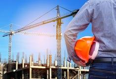 Dirija sostener el casco de seguridad amarillo en sitio de la construcción de edificios con la grúa