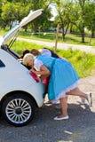 Τρία κορίτσια σε Dirndl που κοιτάζουν σε μια αυτοκίνητο-μπότα Στοκ Φωτογραφία