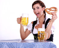 Dirndl. Bavarian brunette woman on blue white table with beer and snack stock images
