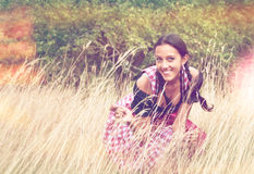 Dirndl d'uso della giovane donna che posa nel campo Fotografie Stock