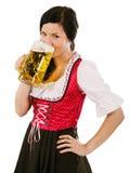 Dirndl que lleva de la mujer y cerveza de consumición de Oktoberfest Imagenes de archivo