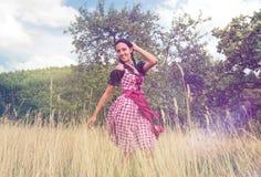 Dirndl vestindo da jovem mulher que levanta no campo Imagem de Stock