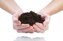 Dirt. Women hand holding soil isolated on white Stock Image