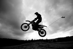 Dirt bike jumping sand dunes - Sihlouette Royalty Free Stock Photos
