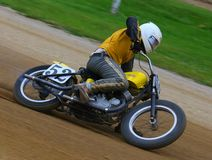 Dirt bike racing. Biker leans his motorcycle as he rides the sharp turn of the dirt track Royalty Free Stock Image
